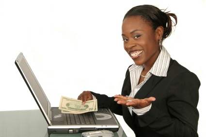 Attractive, smartly dressed african-american woman  behind laptop smiling and showing money and indicating that is easy to be successful